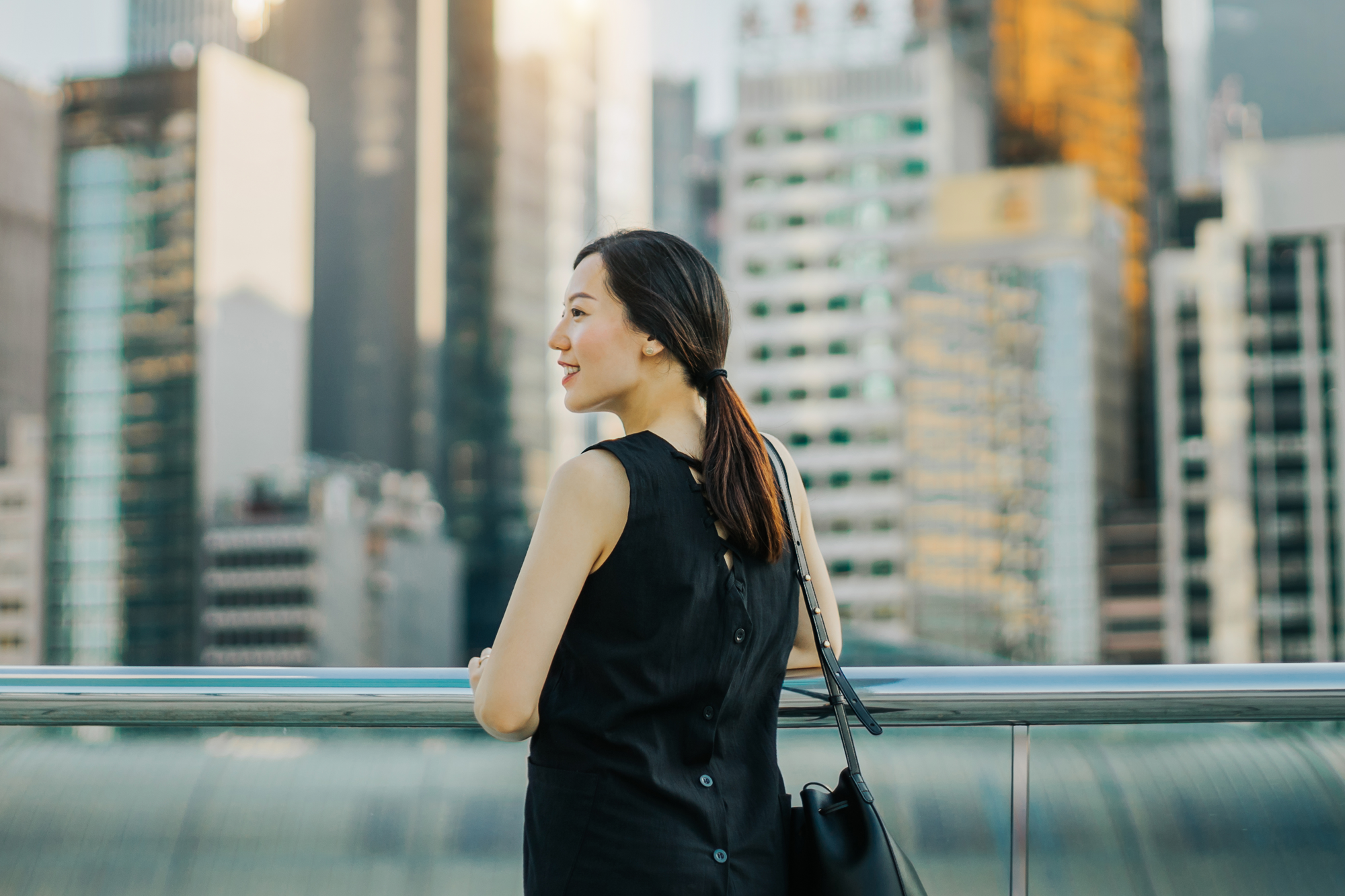 Young Asian woman enjoying the city view during sunset on urban balcony