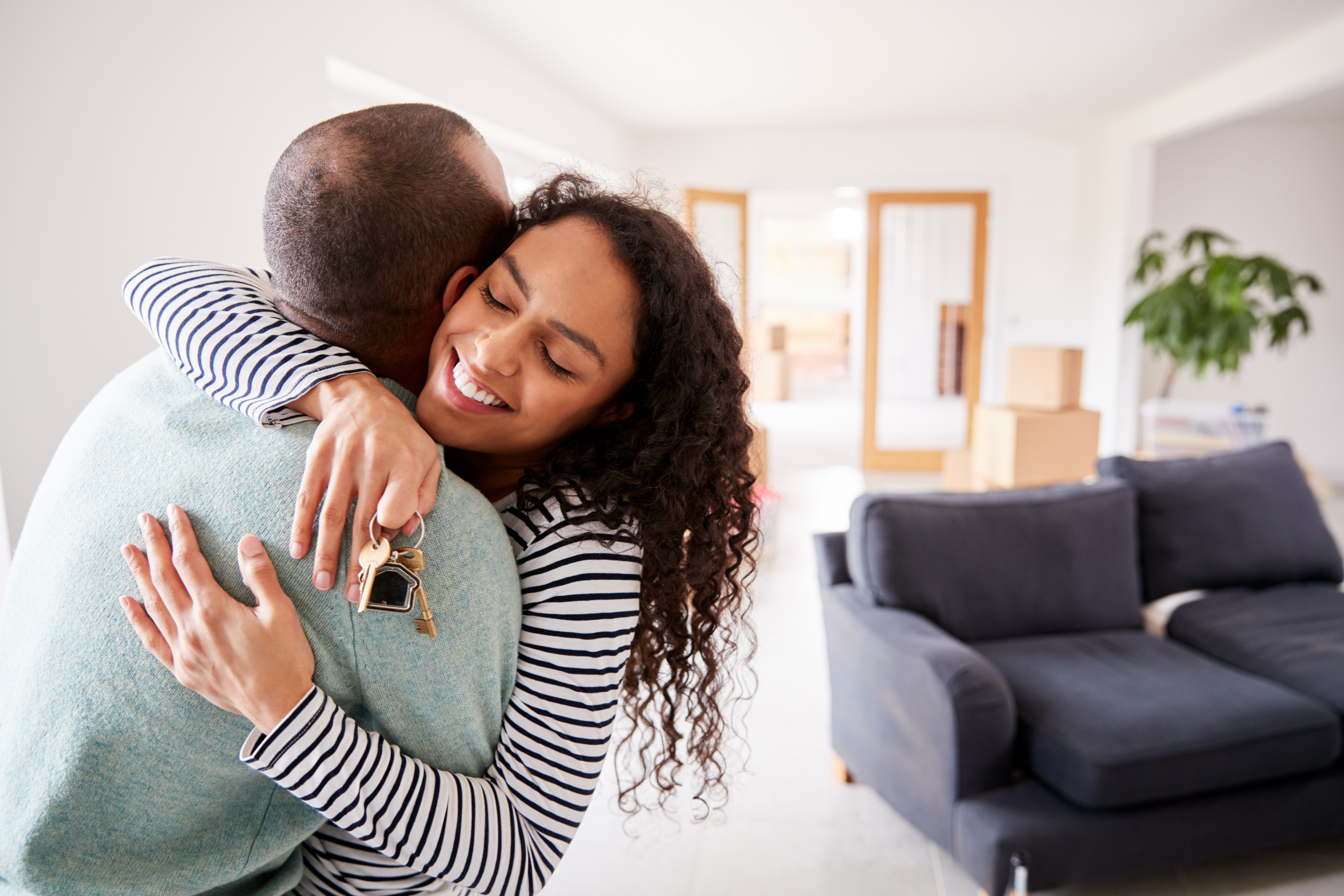 Loving Couple Hugging Holding Keys To New Home On Moving Day